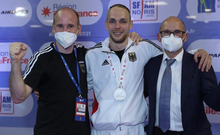 Die Silbermedaille um den Hals und Vorfreude auf Tokio im Kopf: Noah Bitsch, eingerahmt von Vater und Coach Klaus Bitsch (rechts) und DKV-Sportdirektor Christian Grüner